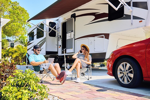Couple With Electronic Devices Sits On Chairs Near Camping Trail