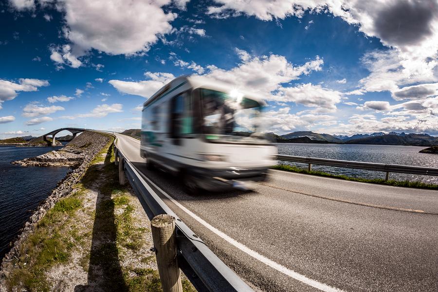 Caravan car RV travels on the highway. Caravan Car in motion blu